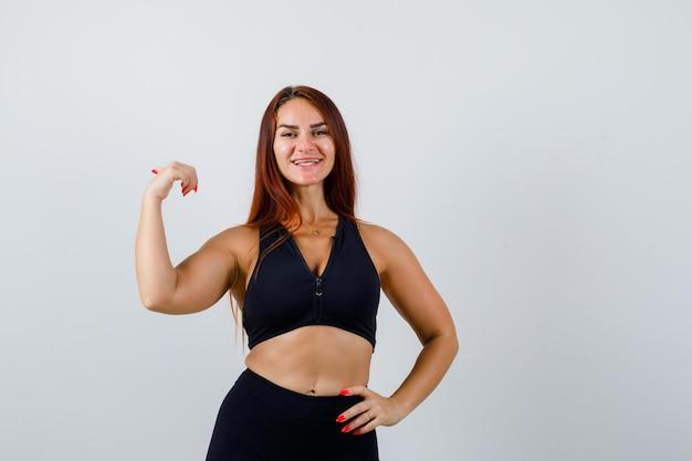 Giovane donna sportiva con i capelli lunghi in un top nero Foto Gratuite