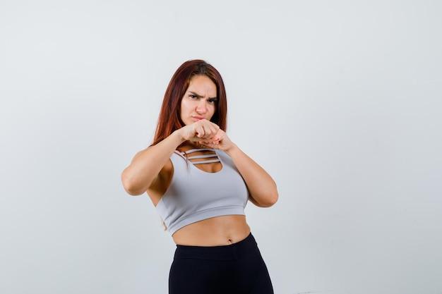 Giovane donna sportiva con i capelli lunghi in un top grigio