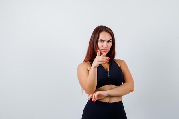 Молодая спортивная женщина с длинными волосами в черном топе