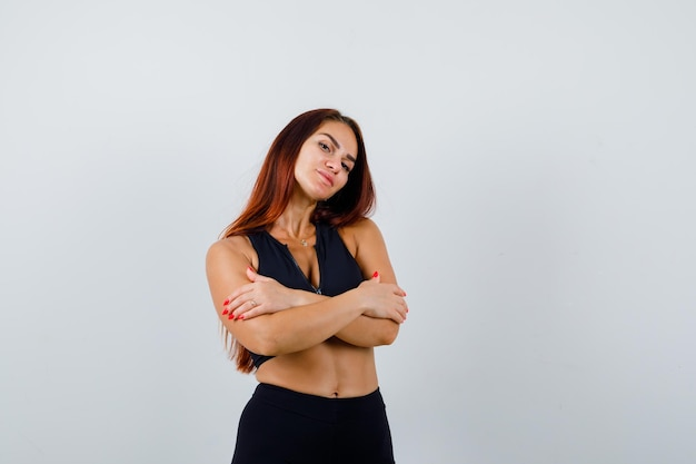 黒のトップで長い髪の若いスポーティな女性