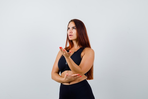 黒のトップで長い髪の若いスポーティな女性 無料写真