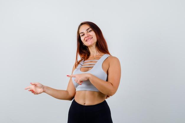 Молодая спортивная женщина с длинными волосами в сером топе