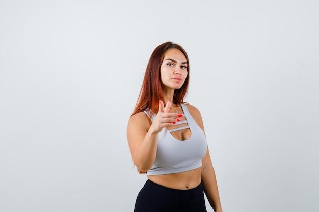 灰色のトップで長い髪の若いスポーティな女性