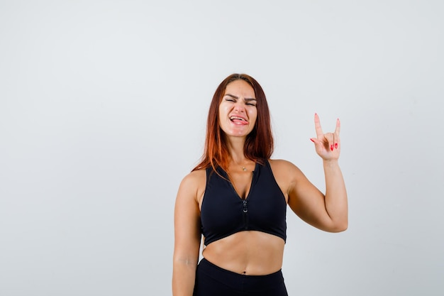 Young sporty woman with long hair showing rock gesture