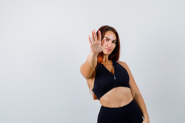 Young sporty woman with long hair showing stop gesture