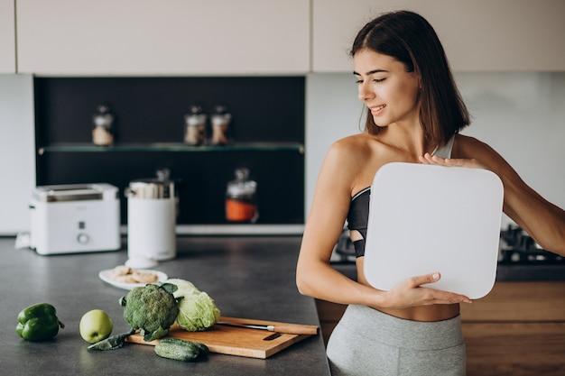 Молодая спортивная женщина с весами на кухне