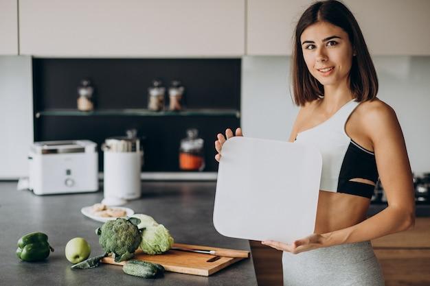 キッチンで体重計を持つ若いスポーティな女性