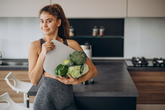 Young sporty woman with scales and vegetables at the kitchen