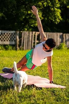 Молодая спортивная женщина с короткими черными волосами делает планку на коврике для йоги на открытом воздухе, тренируется в парке на природе