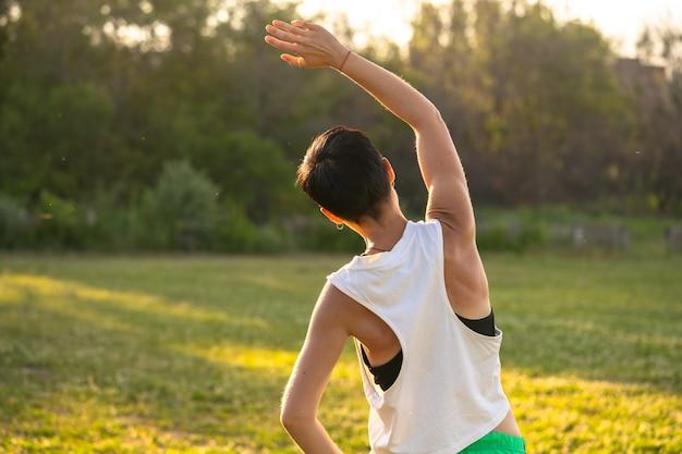 Молодая спортивная женщина с короткими черными волосами растягивается перед бегом в парке, разминается перед тренировкой на открытом воздухе