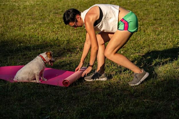 Молодая спортивная женщина с короткими черными волосами тренируется на открытом воздухе на коврике для йоги на зеленой траве в парке, занятия с собакой, прогулка джек-рассел-терьера