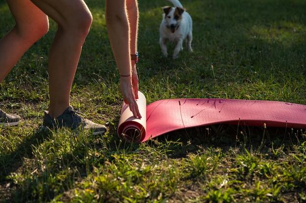 Молодая спортивная женщина с короткими черными волосами разворачивает коврик для йоги для упражнений на расслабление в парке на зеленой траве, тренируясь на открытом воздухе
