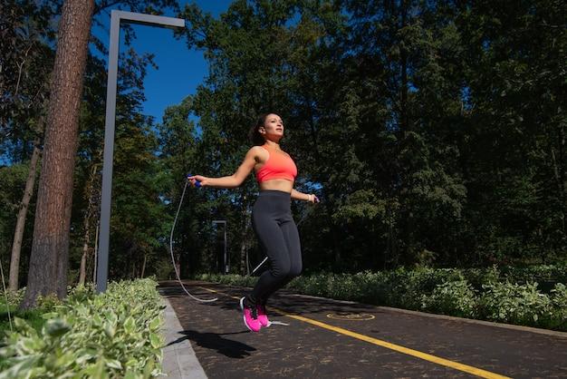 自然の中で屋外で縄跳びの若いスポーティな女性。スポーツ、屋外フィットネス