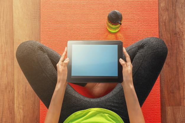 요가 매트에 앉아 태블릿 pc와 스포티 한 젊은 여자. 휴식과 일의 균형 개념