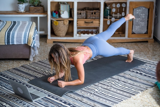 Young sporty woman working out at home teenager doing fitness exercises on living room floor for buttocks body shaping using online personal training program with laptop doing push ups pilates
