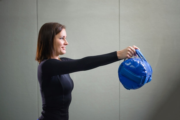 Young sporty woman working out with fitness bag at gym
