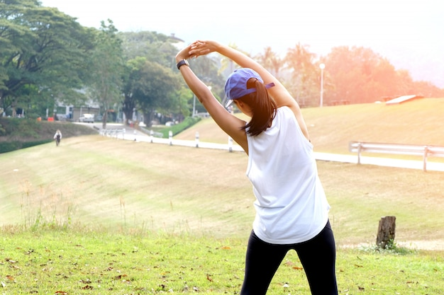 Young sporty woman workout before fitness training warming up in outdoors.