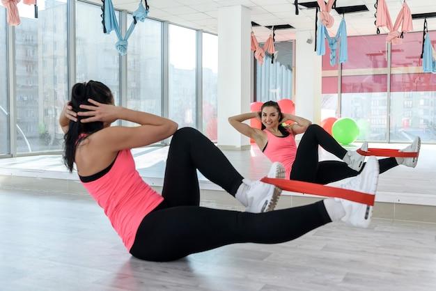 스포티 한 젊은 여성 운동 체육관에서 탄력 붕대를 행사. thealhty 라이프 스타일을위한 운동 운동을하는 소녀. 여자 선수