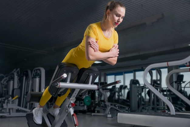 Young sporty woman workout on exercises machine in gym