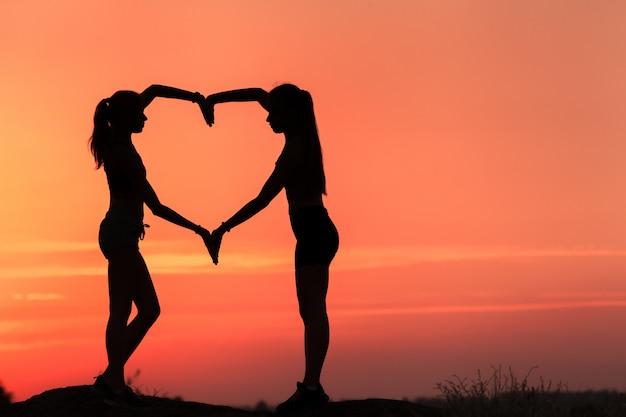 夕暮れ時のハートの形で手を繋いでいる若いスポーティな女性