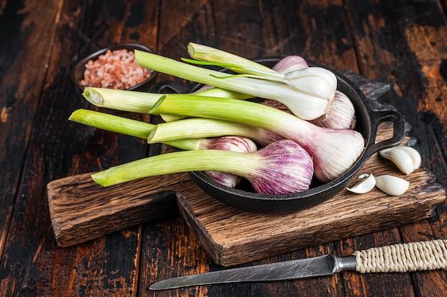 Молодые весенние луковицы чеснока и гвоздики в сковороде. темный деревянный фон. вид сверху.