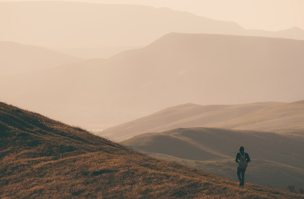 Молодой стоящий человек с рюкзаком. путешественник на камне на берегу моря в красочном закатном небе. красивый пейзаж со спортивным мужчиной качает море и облака на закате. спортивный образ жизни