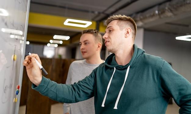 彼らの仕事を計画している若いスタートアップチーム。ホワイトボードに多くのメモを載せた創造性ワークショップのブレーンストーミングプロセス。