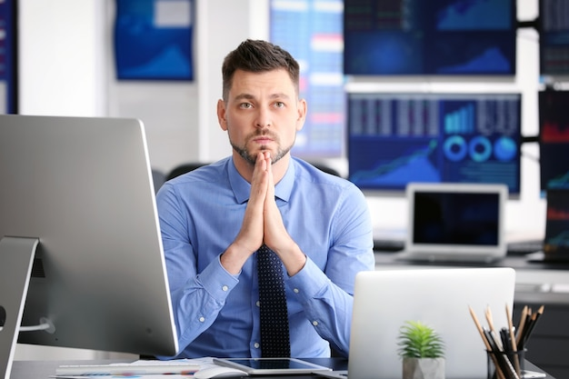 Молодой биржевой трейдер, работающий в офисе