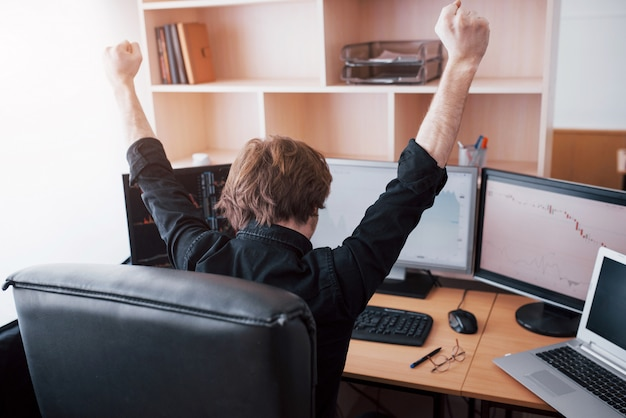 Young stock trader broker stretching hands at workplace, he first achieved great success on the stock market