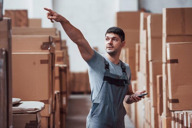 Молодой работник склада в униформе с подставками для телефонов и поднятой рукой.