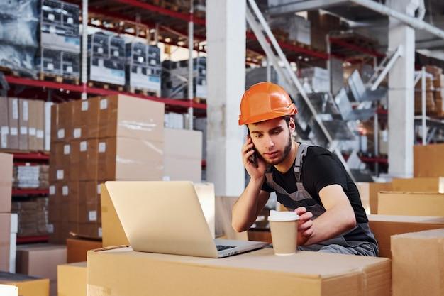 Молодой работник хранилища разговаривает по телефону и сидит возле своего ноутбука и чашки с напитком.