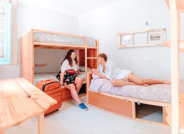 일광에 밝은 호텔 침대에 누워있는 젊은 직선 백인 부부