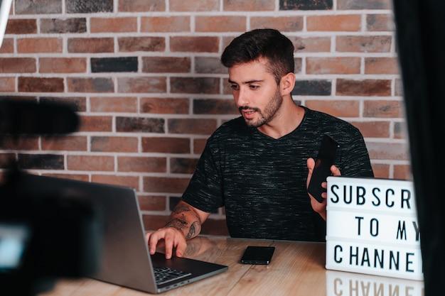 전화 정보를 읽기 위해 컴퓨터를 보고 있는 20대 젊은 스트리머 소년