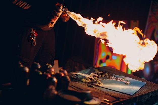 어두운 밤에 스프레이 컬러 페인트와 불로 자신의 작품을 마무리하는 젊은 거리 예술가