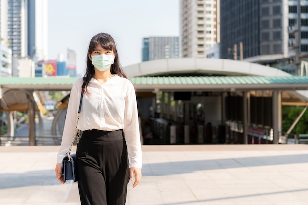 Young stress asian businesswoman in white shirt going to work in pollution city she wears protection mask prevent dust and covid-19 with business office building in bangkok, thailand.