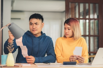 Young stressed asian couple managing finances, reviewing their bank accounts using laptop computer