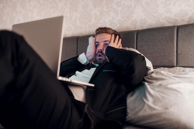젊은 사업가 무릎에 노트북과 얼굴에 손을 호텔 방에 침대에 누워 강조했다. 과로 개념.