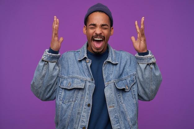 若い強調された暗い肌のひげを生やしたブルネットの男は、紫色の壁の上でポーズをとって、上げられた手で猛烈に叫びながら目を閉じたままにします