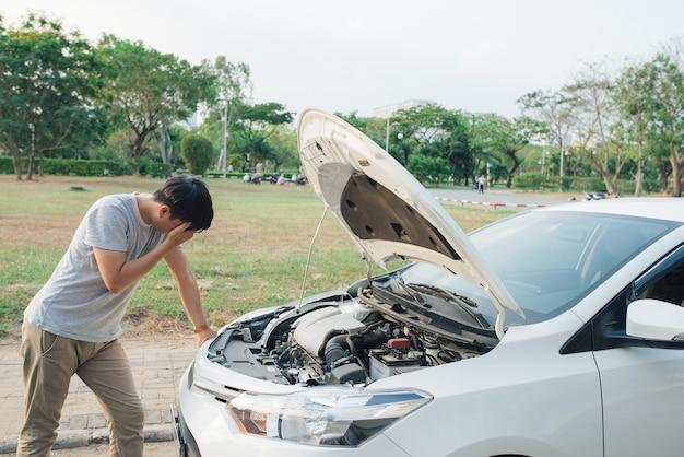 고장난 엔진을 보고 좌절감을 느끼며 고장난 차에 문제가 있는 젊은 스트레스