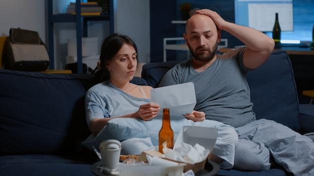 Молодая напряженная супружеская пара начинает плакать, сидя на диване с газетами и читая плохие новости в ...