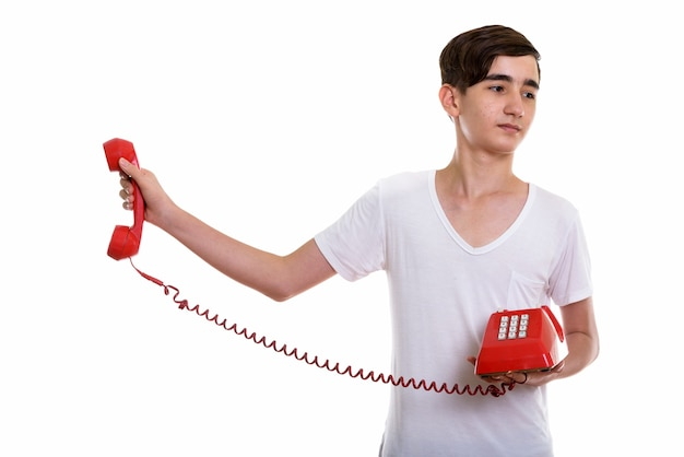 若いは古い電話を保持しているペルシャの10代の少年を強調