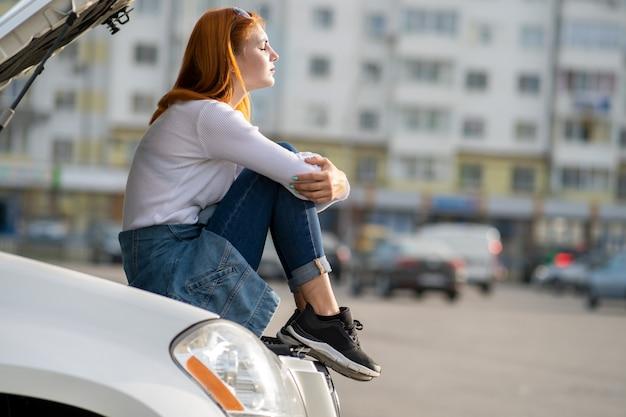 若者は、ボンネットが飛び出し、助けを待っている壊れた車の近くで女性ドライバーを強調した。