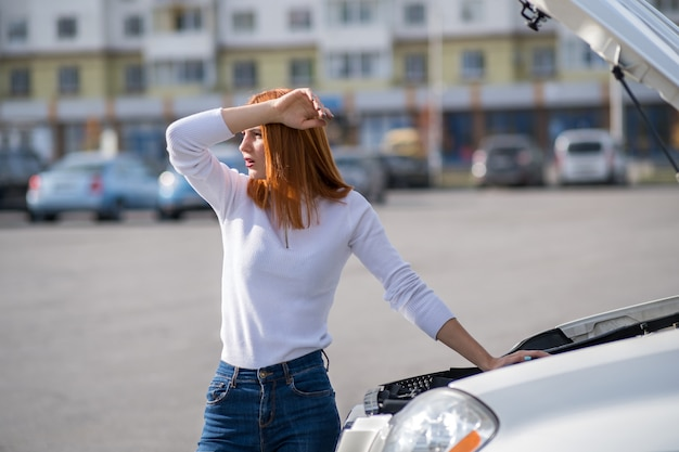 Young stressed woman driver standing near broked car with open hood.