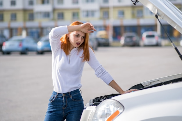 Молодой подчеркнутый водитель женщины, стоящий около сломанной машины с открытым капотом