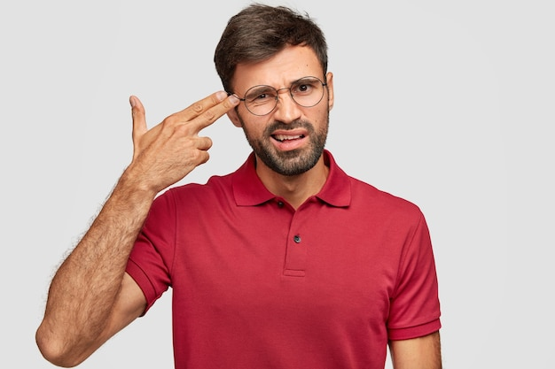 Young stressful male makes gun gesture, pretends commiting suicide, keeps two fingers on temples, feels desperate, poses alone against white wall, dressed in casual red t-shirt, has crisis