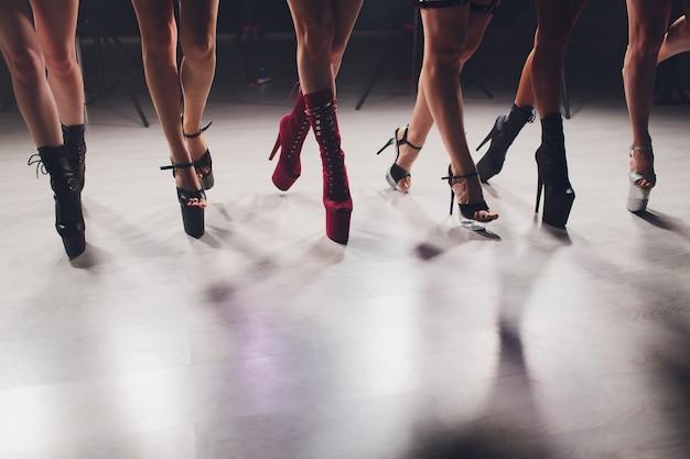 Молодой стриптиз танцор движется в туфлях на высоких каблуках на сцене в стриптиз ночной клуб, полюс танцы.