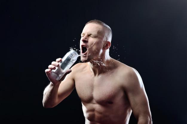 Молодой сильный спортсмен жадно пьет воду из пластиковой бутылки на темном студийном фоне. вода плещется вокруг парня.