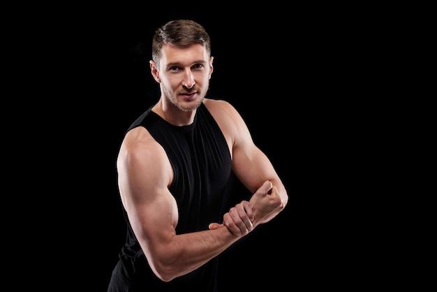 그의 힘을 보여주는 동안 한 손을 다른 손목에 유지하는 검은 색 운동복의 젊은 강한 운동 선수