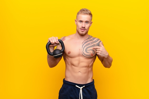 Young strong blonde man looking happy, proud and surprised, cheerfully pointing to self, feeling confident and lofty with a dumbbell