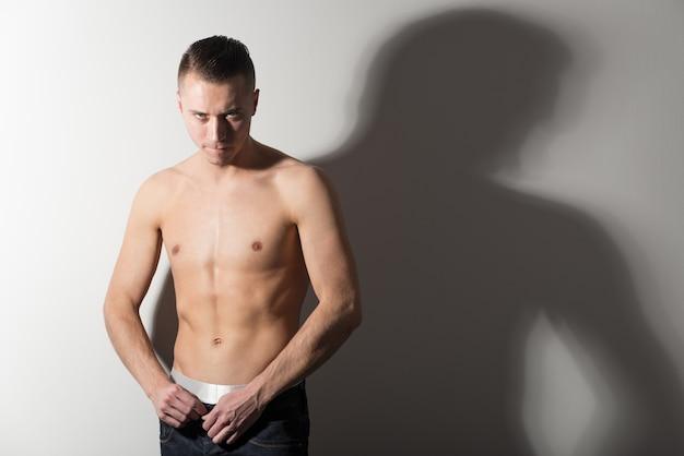 立って彼の体を見せている茶色のパンツの若い強い白人男性モデル